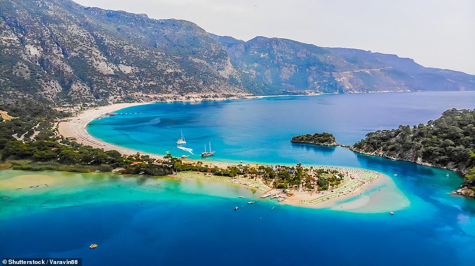 Top of the world: Babadag mountain overlooks Oludeniz beach (pictured) and the blue lagoon. Paragliders from all over the world travel to this spot to take to the skies