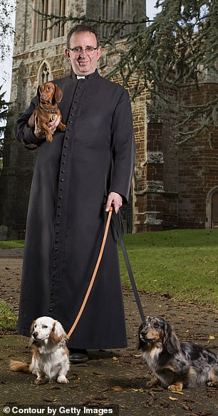 Richard Coles is pictured above with his dogs