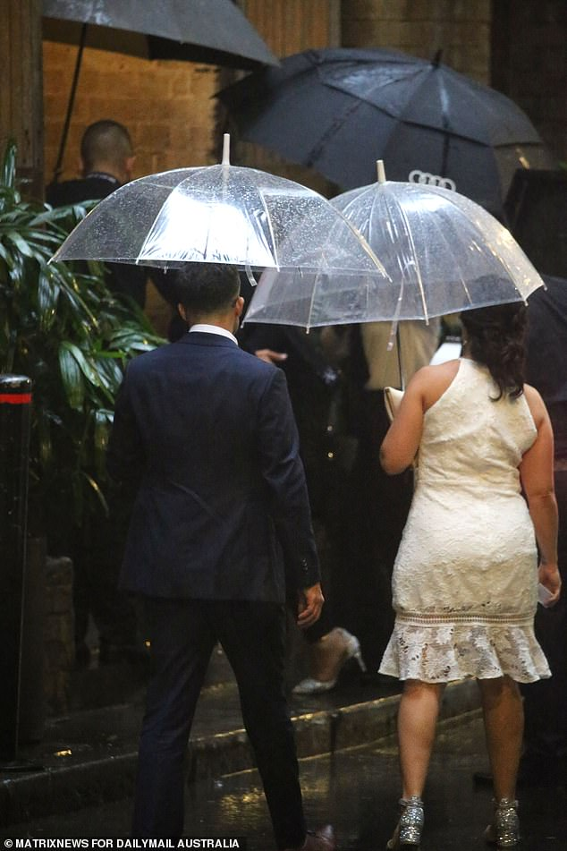 Staying dry: A man and a woman arrived holding an umbrella each