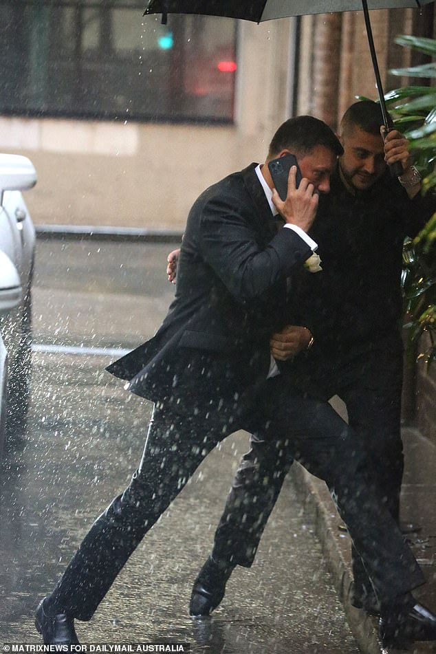 Well he looks good!u00A0Looking slick in a slim-fit suit, the businessman was helped by a minder who held an umbrella over his head. He took a call as he raced indoors