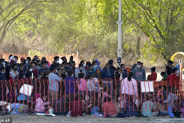 Migrants are seen in custody at a US Customs and Border Protection processing area under the Anzalduas International Bridge on Friday in Texas
