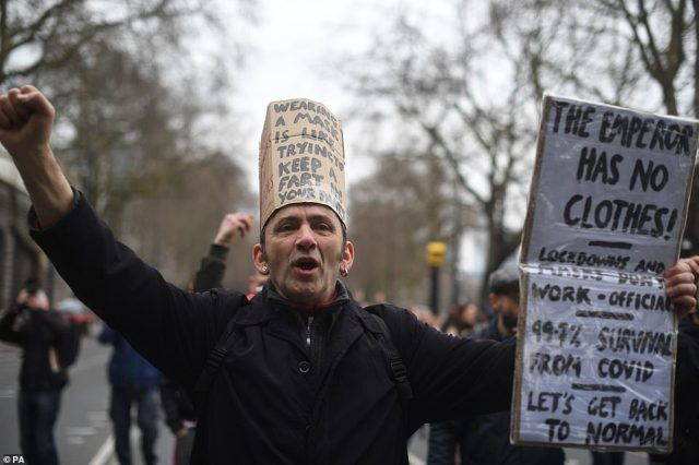 A protester holds a sign reading: 'The emperor has no clothes! Lockdowns and masks don't work. 99.7% survival from Covid. Let's get back to normal'