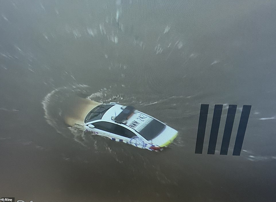 A police car was inundated in floodwaters in Freemans Reach in Sydney's north-west on Sunday
