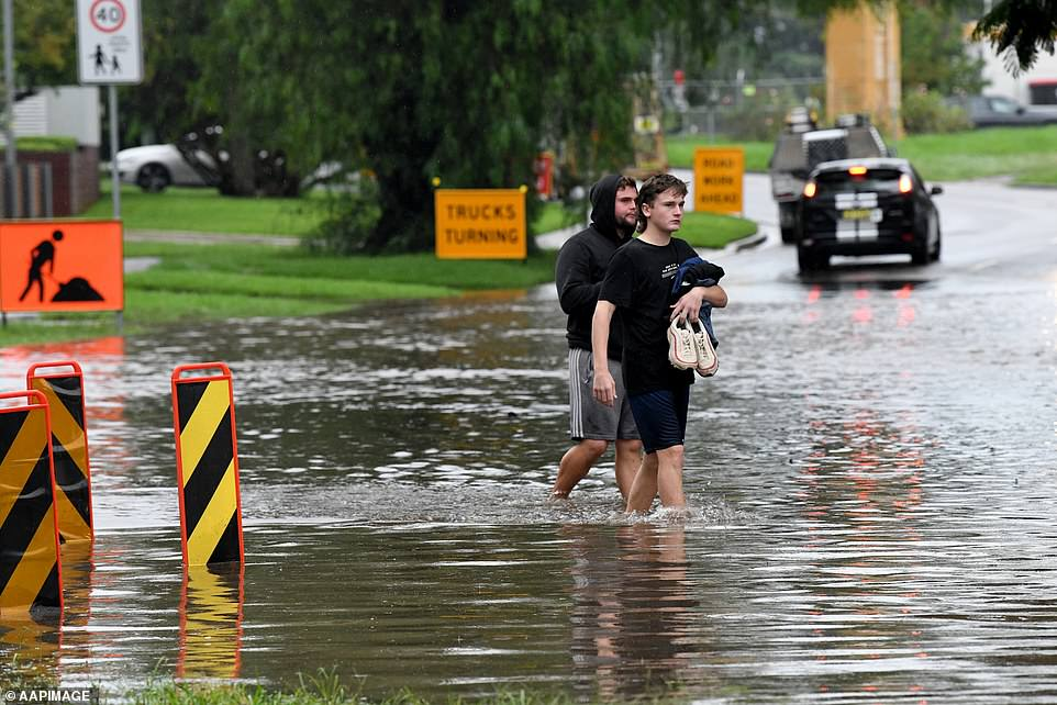 Hundreds of Penrith residents spent the night in evacuation centres or alternative accommodation after their homes came under threat from floodwater. Pictured are residents wading through a submerged Ladbury Ave in Penrith