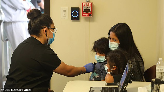 A woman and two children receive an examination at the El Paso Service Processing Center in Texas on March 8