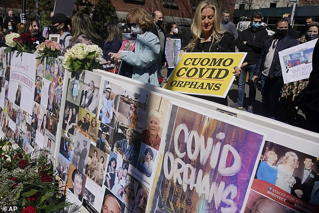At the memorial wall, dozens of protesters gathered to call for Cuomo's resignation or impeachment - some held signs that said they were 'Cuomo Covid Orphans'