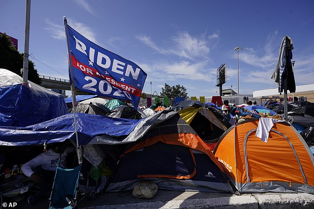 Biden said during his campaign that he would implement 'more humane' border policies. Some images from migrant camps in Mexico show 'Biden' flags (pictured) waving outside tents, illustrating the hopes they have for the new administration