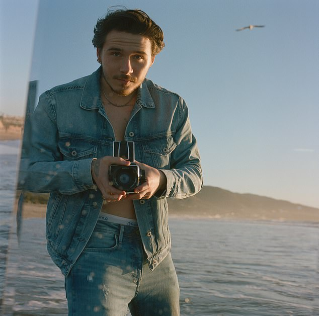 Snapped at sunset: Brooklyn dons a denim jacket in the shots, over matching jeans. He teases his torso in the images, shirtless under the jacket, Pepe Jeans branded underwear on display