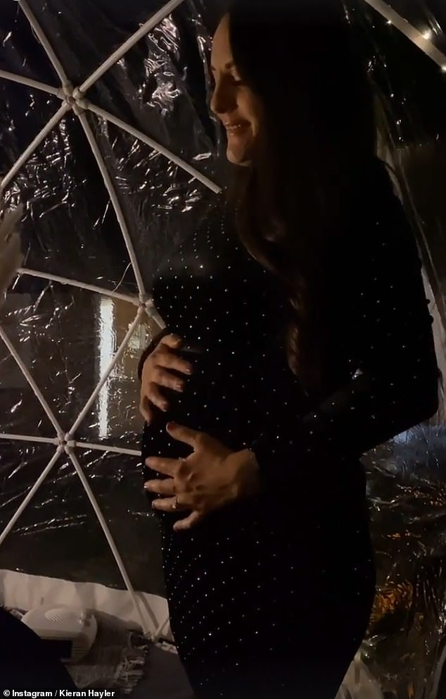 Glowing:The brief video showed Michelle posing in a tight black velvet dress offering a glimpse of her blossoming bump