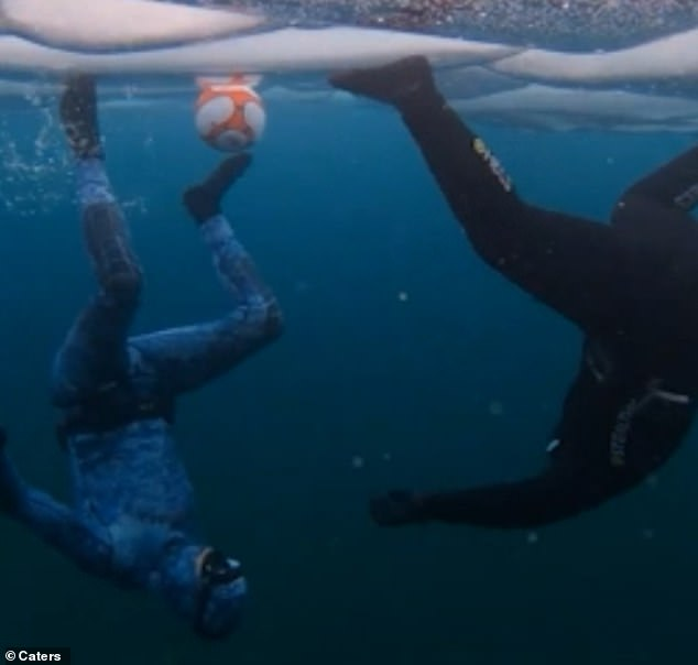 Andrew's wife Lily captured the pair tussling over the soccer ball by walking upside down across the ice while underwater