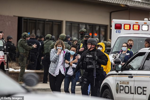Healthcare workers walk out of a King Sooper's Grocery store after a gunman opened fire