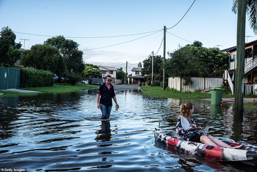 People are seen in a street affected by the flood in Windsor Sydney. Evacuation warnings are in place for parts of Western Sydney as floodwaters continue to rise