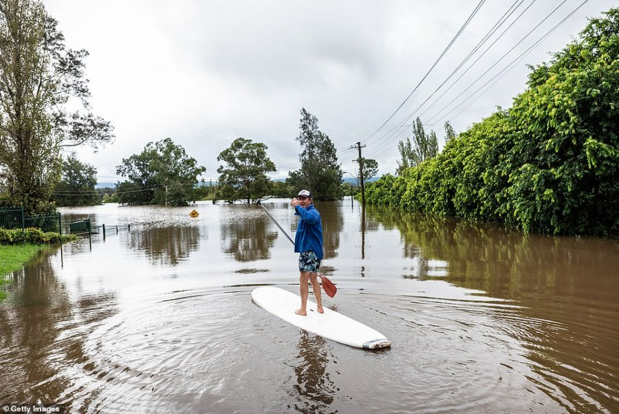 A man is standing on a paddle board in Richmond Sydney. Evacuation warnings are in place for parts of Western Sydney as floodwaters continue to rise