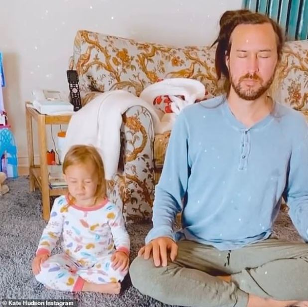 Inhale ... exhale ...: The baby is seen in pajamas as he sits cross-legged next to Danny with his eyes closed and takes a deep breath.