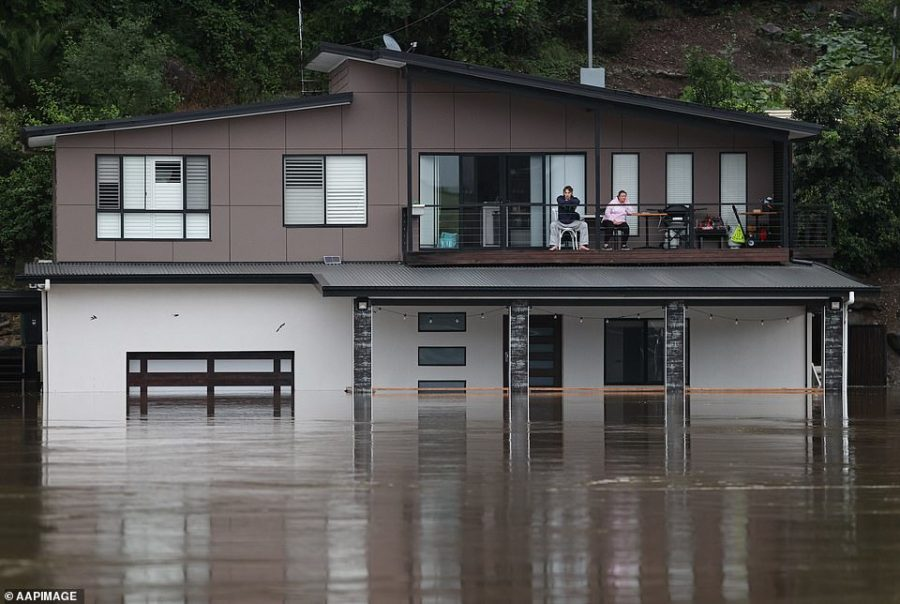 Residents look out at the swollen Hawkesbury River from the deck of a partially submerged house as floodwaters rise