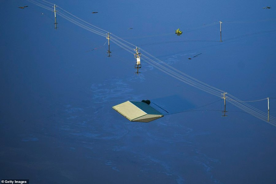 This photo taken above Windsor and the nearby Pitt Town area showed the roof of a property nearly completely submerged