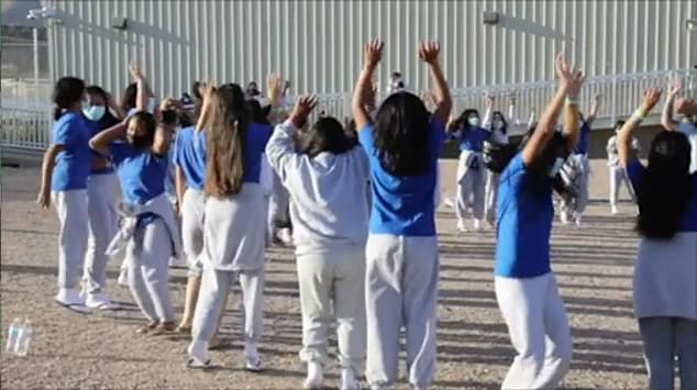The children take part in an outdoor exercise class at the El Paso site in Texas while they await processing