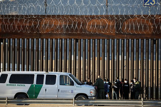Migrants from Central America are detained by U.S. Border Patrol agents as they turn themselves in to request asylum, after crossing into El Paso
