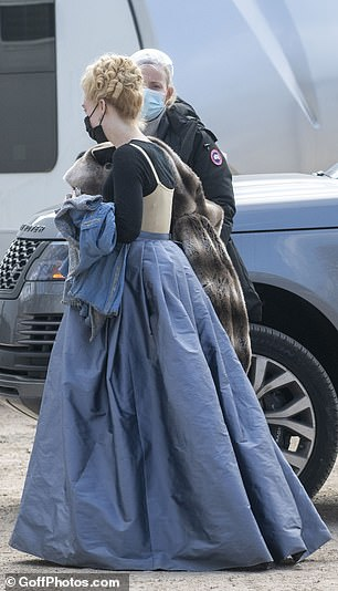 Filming: Elle had in her hand a heavily-embroidered jacket and a faux-fur blanket