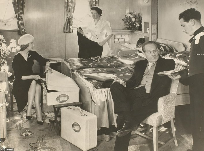 Regal: Passengers and staff in a luxurious first-class main deck stateroom on the Queen Mary. The image was taken at some point in the 1960s