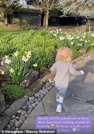 Adorable: The toddler dashed around their new garden discovering the pretty flowerbeds