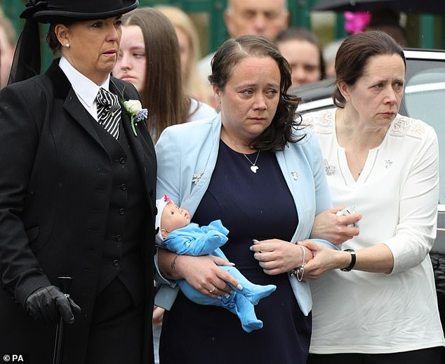 Mylee Billingham's mother Tracey Taundry holding a doll as she arrived at the funeral of the eight-year-old stabbing victim at St James' Church, Walsall, in April 2018
