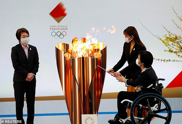 Tokyo 2020 President Seiko Hashimoto looks on as actor Satomi Hishihara and Paralympian Aki Taguchi light the celebration cauldron on the first day of the Tokyo 2020 Olympic torch relay in Naraha, Fukushima prefecture, Japan, March 25, 2021