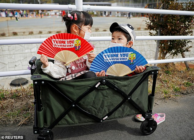 Children wearing face masks hold fans as they wait along the route of the Tokyo 2020 Olympic torch relay