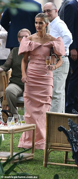 Cheers: The racing heiress was spotted holding a glass of Champagne as she walked through the reception