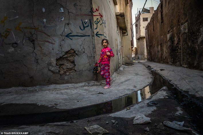A shot showing a little girl walking back home from a store through a dark alley in a destroyed neighbourhood. Thijs said: 'I found the way her colourful clothes sharply contrasted with the grim background symbolic of children's innocence in these dark episodes of conflict'