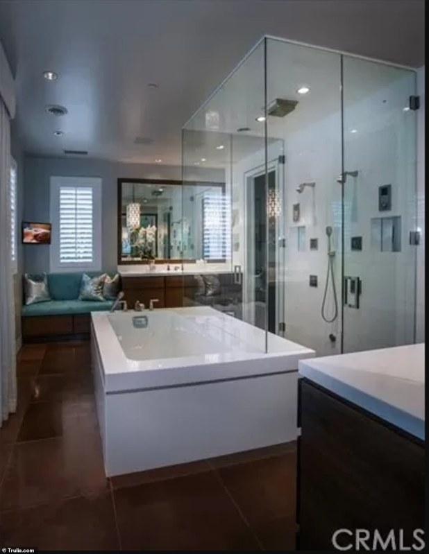 Sophisticated: This bathroom adopts a modern aesthetic with its marble bathtub and glass-enclosed shower.