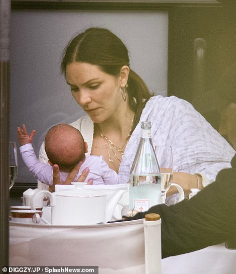 Maternity: The little newborn looked adorable in a shiny white jumpsuit and wiggled into his mother's arms as she continued to pamper him