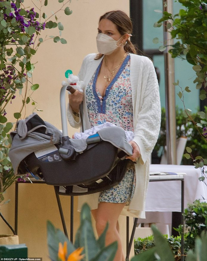 Cozy Boy: Rennie looked incredibly comfortable in her baby carrier, while being wrapped in a white and gray patterned baby blanket