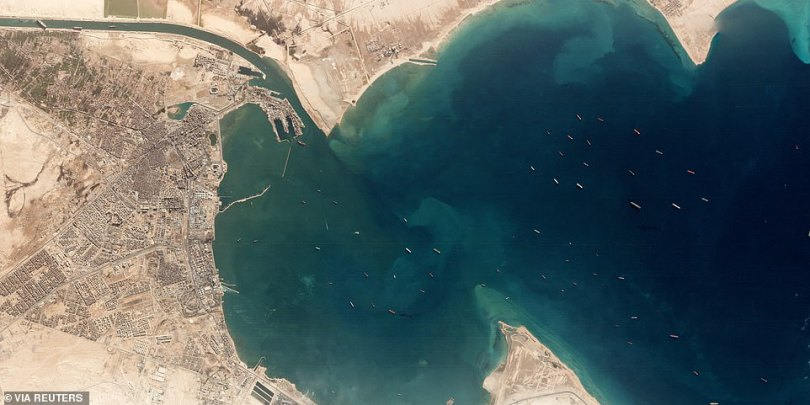 A satellite image taken above the Gulf of Suez where it leads into the Suez Canal (top left) shows at least 50 large ships at anchor as they wait for a stricken container ship to be freed from where it has lodged in the narrow waterway