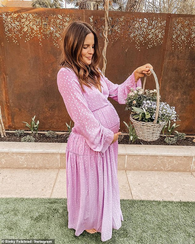 Blossoming: Binky cradled her bump in a pink polka-dot dress as she shared another springtime pregnancy snap to Instagram the day before