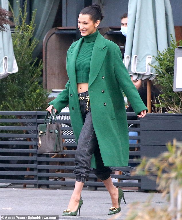 Smiling shoot: Bella Hadid was spotted grinning from ear-to-ear on the set of her latest Michael Kors photoshoot on Thursday clad in a long green coat and midriff-baring turtleneck sweater