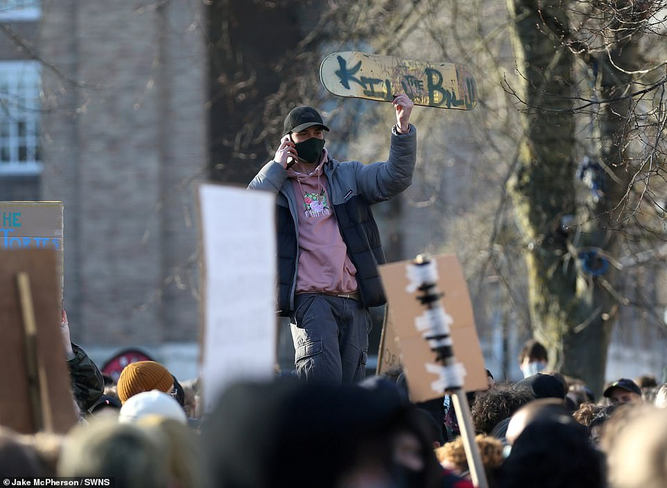 A demonstrator holds a sign written on the underside of a skateboard as hundreds mass on College Green in the city centre