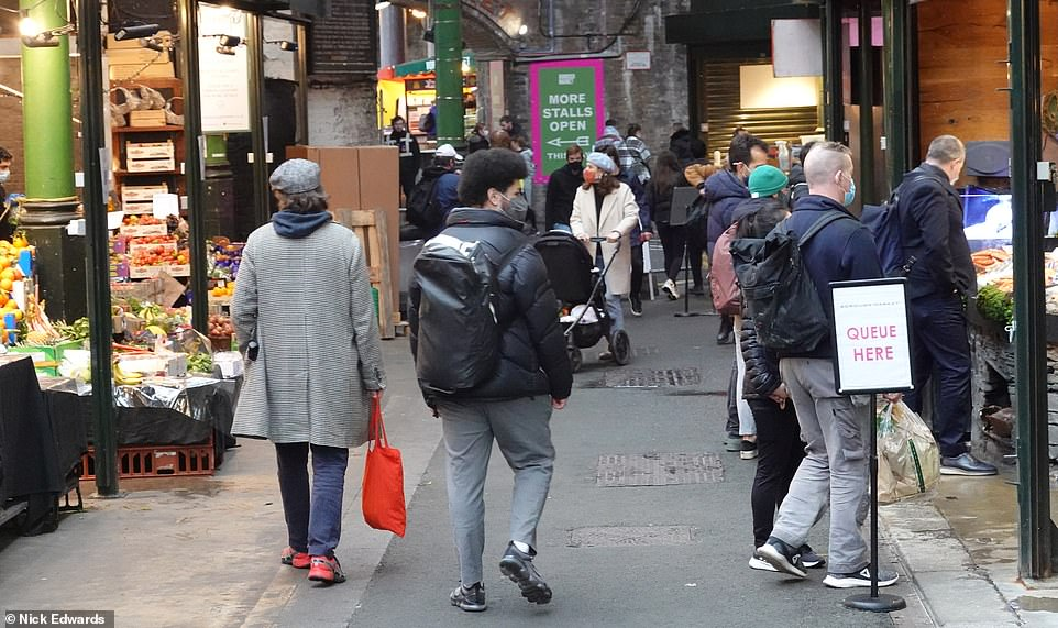 People are pictured walking around Borough Market in central London today as England is still currently in lockdown