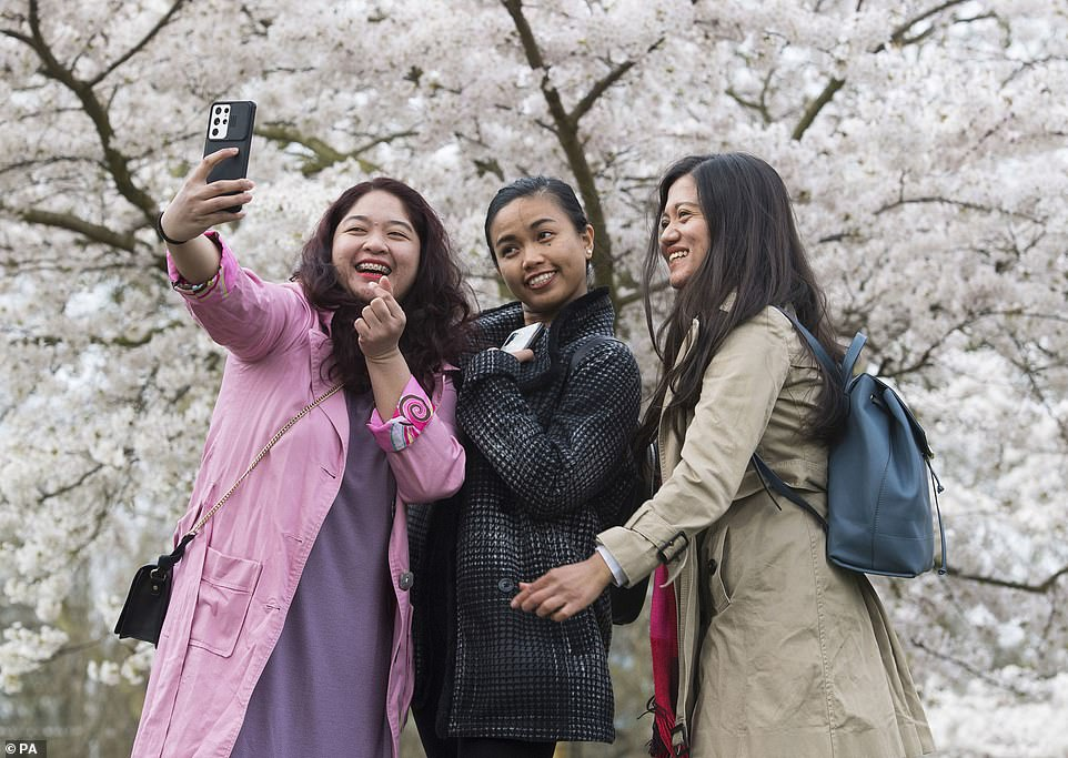 Women posing for a selfie under cherry blossom in Battersea Park, London, on Wednesday as temperatures are set to soar next week