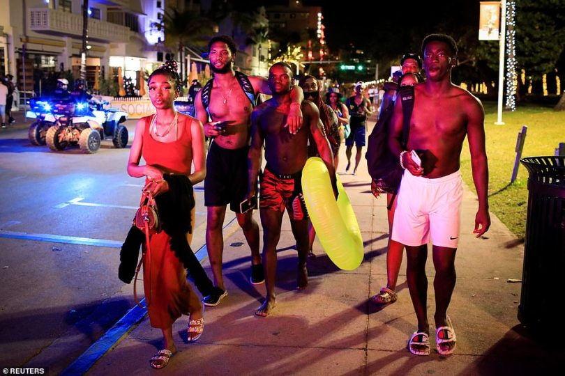 Revelers walk away as police officers ask them to leave during an 8pm curfew imposed by local authorities on spring break festivities