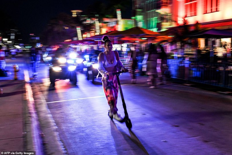 A woman rides a scooter as police ride behind her enforcing the curfew