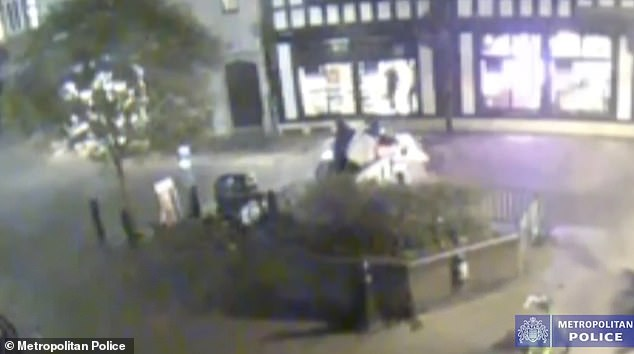 The moped is seen outside the perfume store after the break-in in footage released by the Metropolitan Police