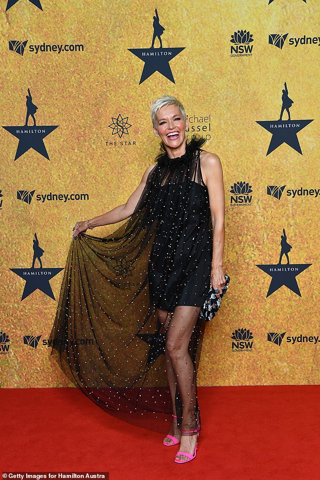Think pink:The 50-year-old beamed as she posed, holding up the sheer material to show off her neon pink heels