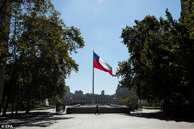 Chile's world-leading coronavirus vaccination rollout is failing to halt the spread of Covid-19 as the majority of the country goes into lockdown. Pictured: A man passes in front a Chile's national flag prior the start of a quarantine period to slow the spread of the coronavirus, at a square in front of la Moneda Presidential Palace in Santiago, Chile, 26 March 2021