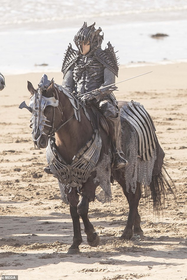 Ready for battle:The men riding the horses were kitted out in elaborate armour made of frightening skeletons as they galloped along the windy British shores