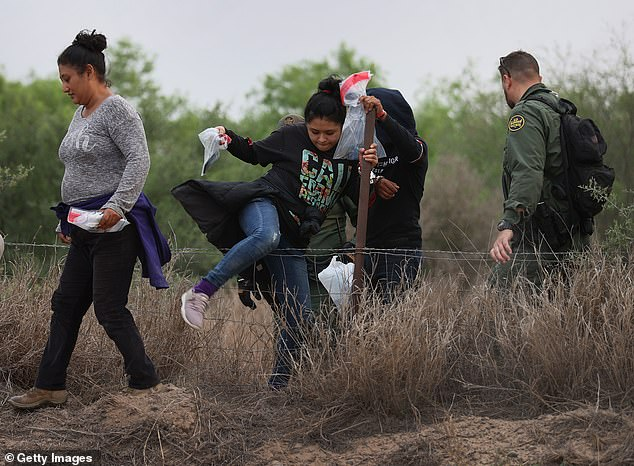 A group of people climbs over a fence as they walk with a U.S. Border Patrol agent after being caught crossing the border from Mexico on Saturday in Penitas, Texas