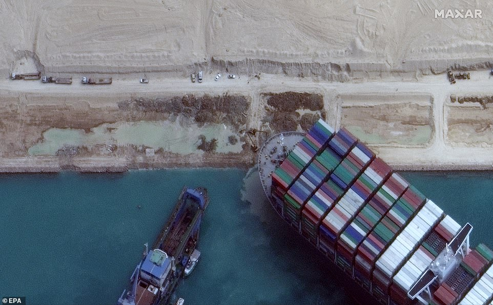 A handout satellite image made available by MAXAR Technologies shows excavation around the bow of the Ever Given and dredging operations in progress, in the Suez Canal, Egypt,March 28, 2021