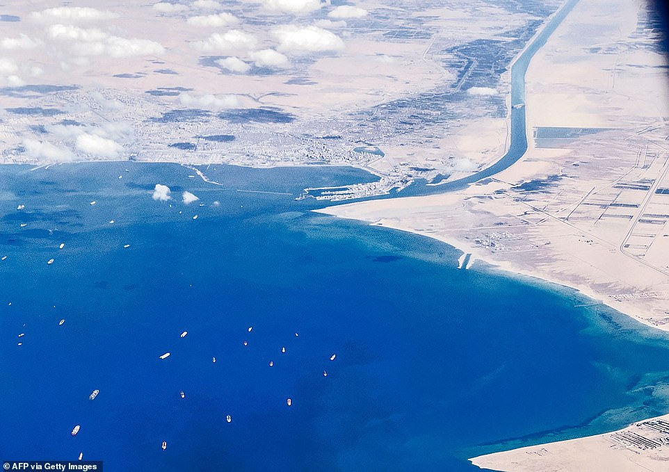 An aerial view taken on March 27, 2021 from the porthole of a commercial plane shows stranded ships waiting in queue in the Gulf of Suez to cross the Suez Canal at its southern entrance near the Red Sea port city of Suez