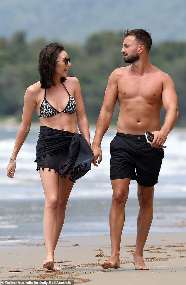 Cute:Meanwhile, Roger oozed confidence in a pair of black swimming shorts, flaunting his washboard abs and muscular arms as he waltzed down the beach with his bride