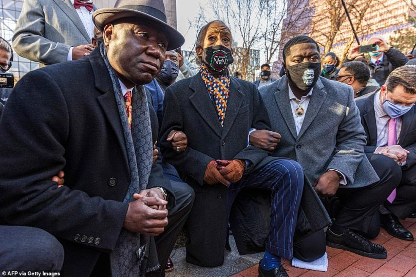 Floyd family lawyer Ben Crump (left) and Rev Al Sharpton, the founder and President of National Action Network,(center) and George Floyd's nephew Brandon Williams (right) kneel outside the Hennepin County Government Center on Monday